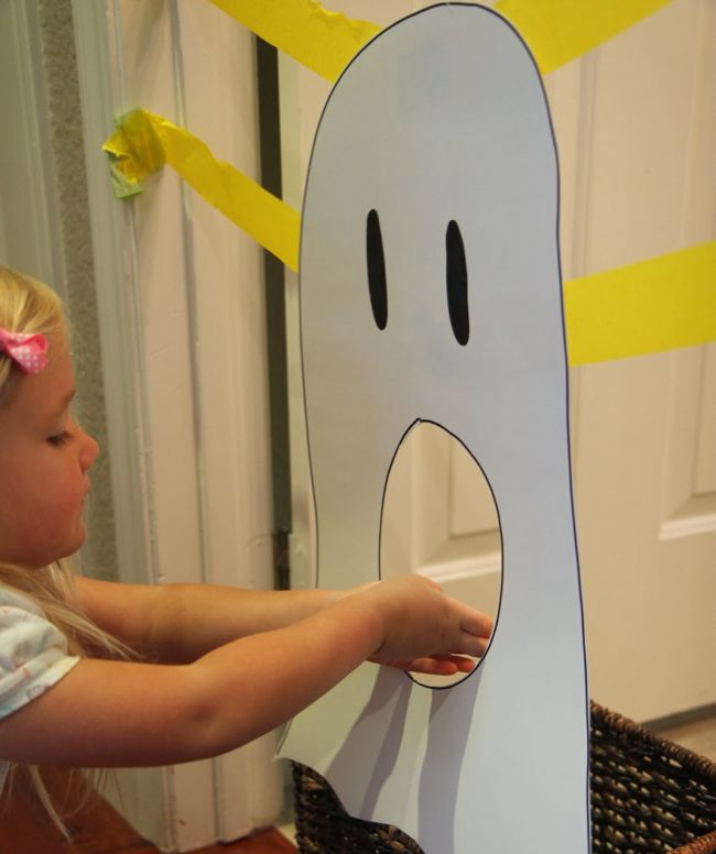 Young student feeding construction paper letters through a large paper ghost's mouth (Halloween Activities)