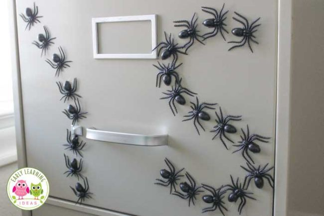 Plastic spider magnets on a filing cabinet spelling out I and S