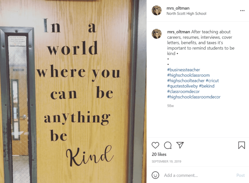 """A brown classroom door with a thin vertical widow with the phrase """"In a world where you can be anything be kind"""" in black letters."""