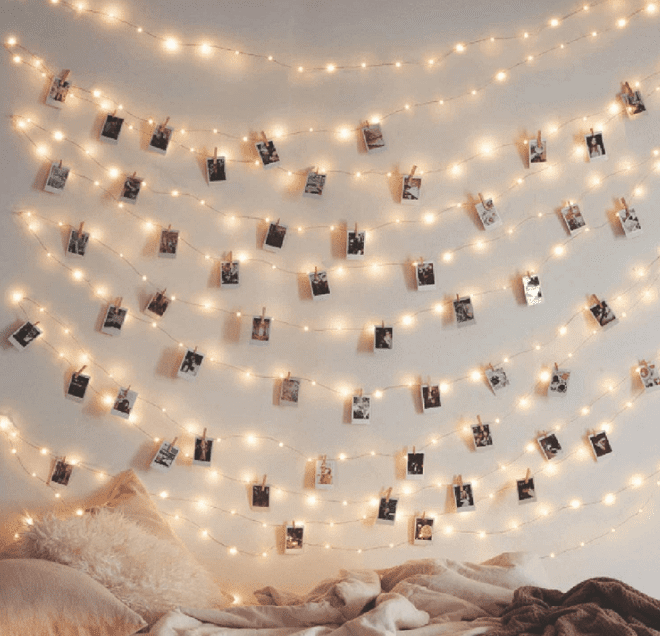 White, decorative string lights are hanging horizontally across a white wall with blankets at the bottom, , as an example of high school classroom decorations