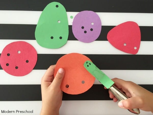A child's hands punch holes into construction paper shapes on a background of black and white stripes