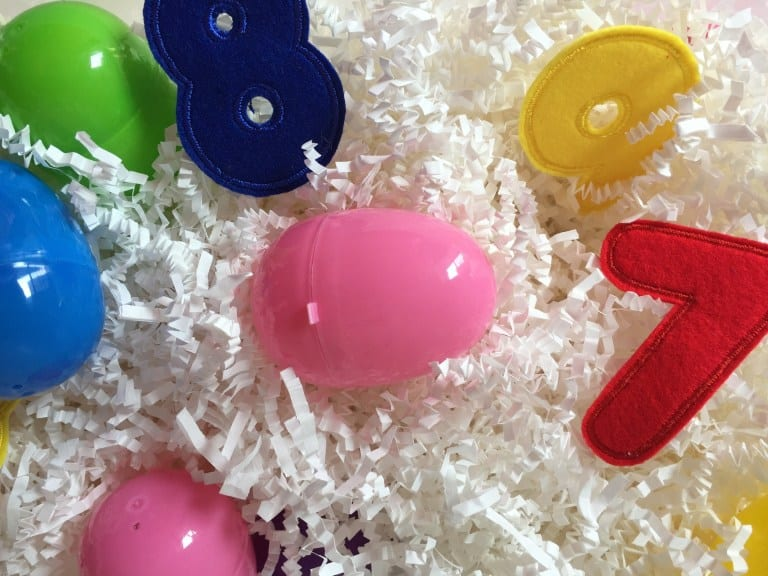 Sensory bin filled with plastic eggs and felt numbers.