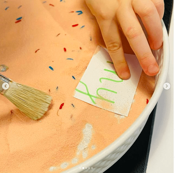"Pink salt in a tray with colored sprinkles and a child's hand holding a paintbrush to brush salt off a card with the sight word ""my"""