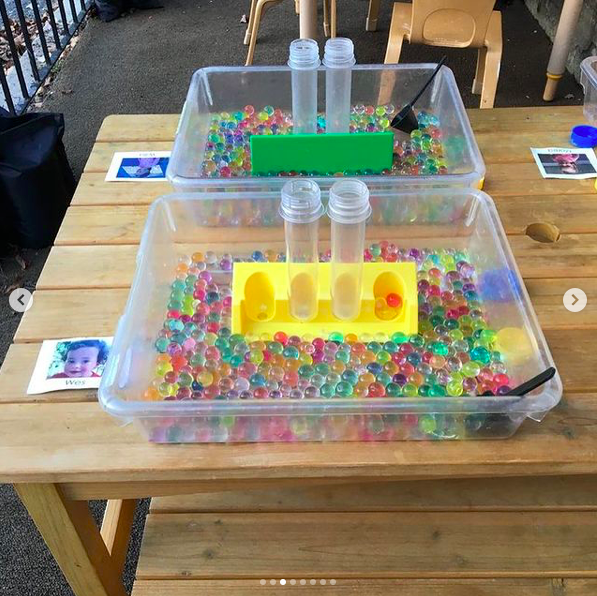 Sensory tubs with water beads and plastic containers labeled with children's photo name cards for individual sensory play in the classroom