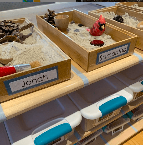 Wooden trays with sand and nature items labeled with student names for individual sensory play in the classroom