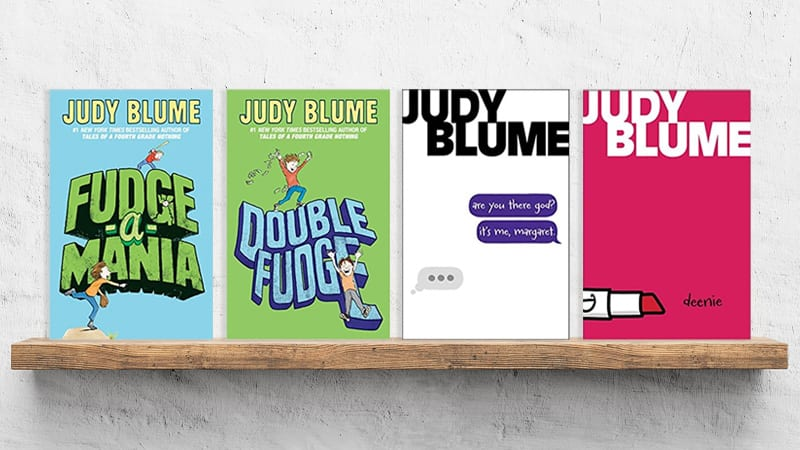 Four Judy Bloom books set on a wooden shelf in a classroom.