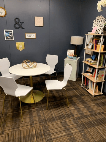 a collaborative workspace with a white table and 4 white chairs and a bookcase filled with books and accessories.
