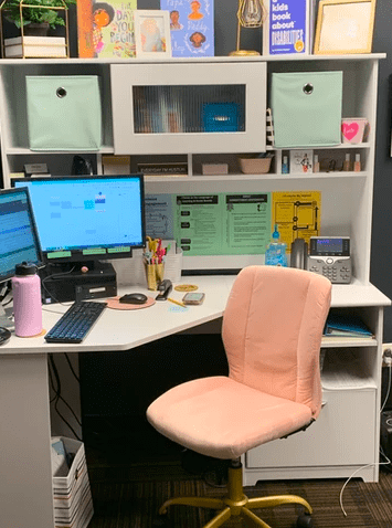 a principal's work area with white desk and bookcase and a pink rolling office chair