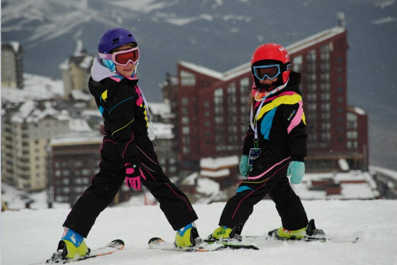 Children in their ski suits on top of the mountain
