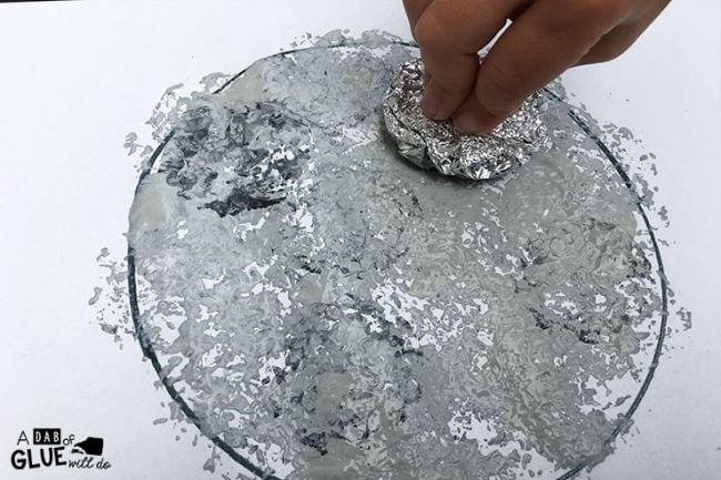 Child's hand using foil ball dipped in paint to create a moon painting