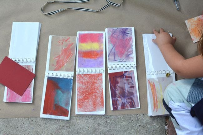 Child sliding pastel art into mini photo album pages (Kindergarten Art)