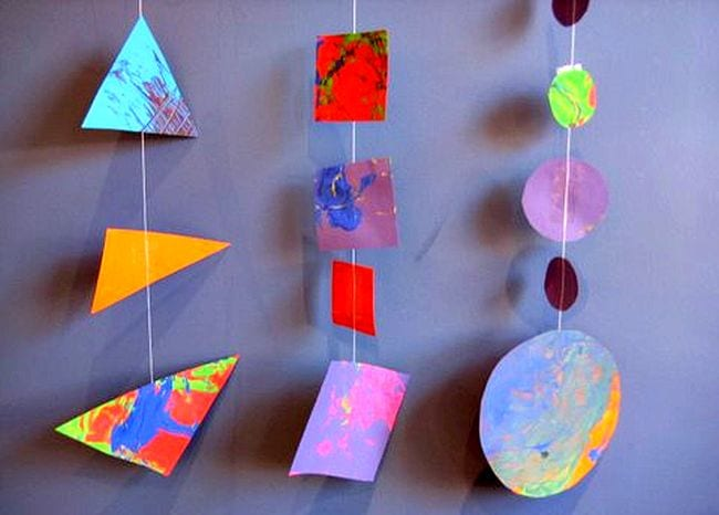 Colorful painted triangles, squares, and circles strung on garlands