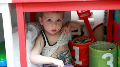 Portrait of boy covered in paint under table - incoming kindergarteners need key life skills