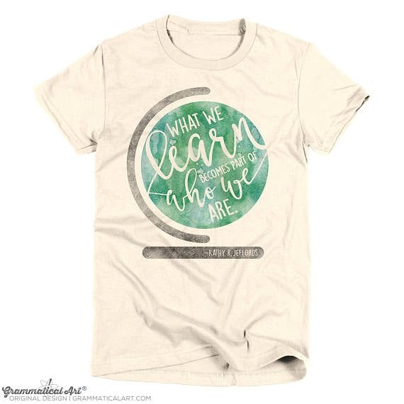 """Teacher shirt saying """"what we learn becomes a part of who we are"""" on a globe"""