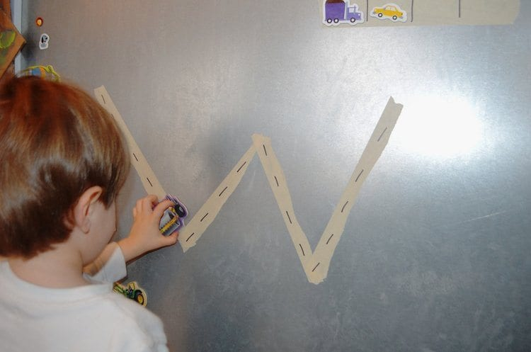 The letter W taped with masking tape onto a metal board