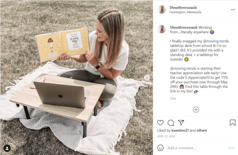 Teacher sitting with laptop on portable desk outside on blanket