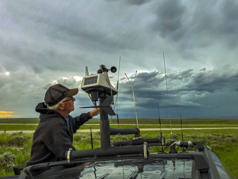 Storm-chaser adjusts the rooftop weather station on his chase vehicle as a severe storm builds in the background- science careers