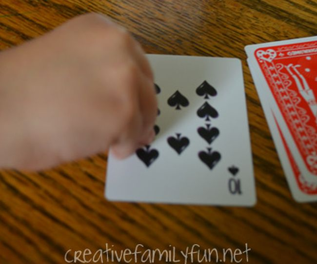 Child flipping a playing card from a deck (Math Card Games)