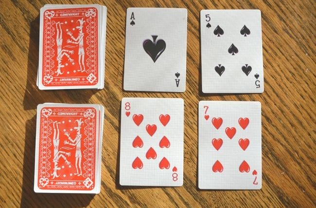Two stacks of cards with two cards laid face up next to each
