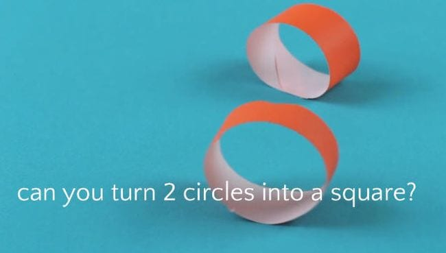 Two orange loops made of strips of paper on a blue background. Text reads Can you turn 2 circles into a square?