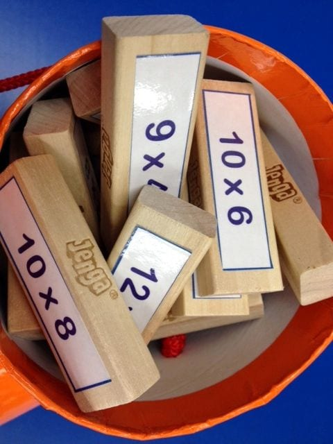 Jenga pieces with multiplication problems on them.