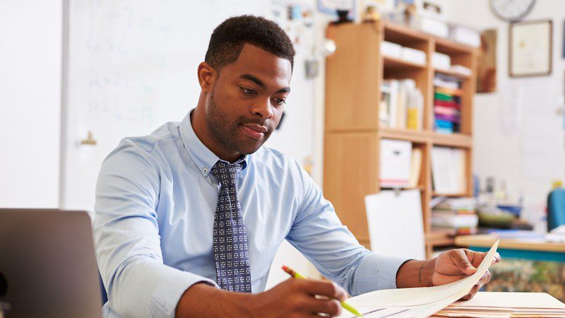 Teacher at a desk looking at a document