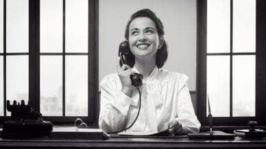 No emails parent teacher --Smiling vintage receptionist working at office desk and smiling-