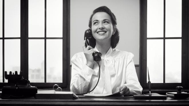 No emails parent teacher --Smiling vintage receptionist working at office desk and smiling-