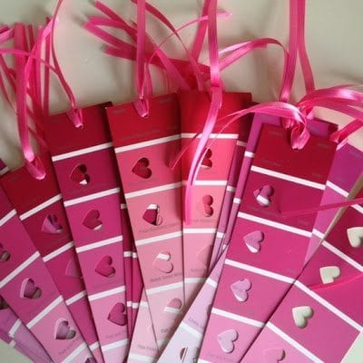 Pile of paint strips in shades of red and pink made into bookmarks with heart-shaped cut outs and pink ribbon on top