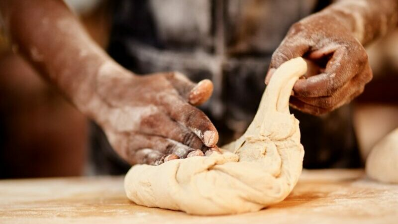 Black hands kneading dough on a board