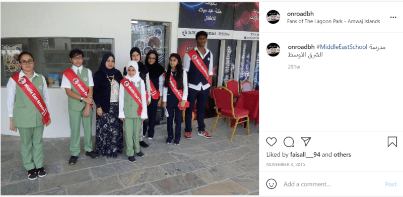 Teacher and students wearing uniforms and sashes at a middle east school