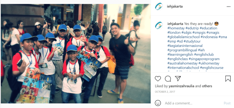 Teacher with students wearing red and white shirts and blue hats on streets of Jakarta