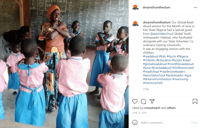 Teacher leading circle time in Nigeria with students in pink and blue uniforms