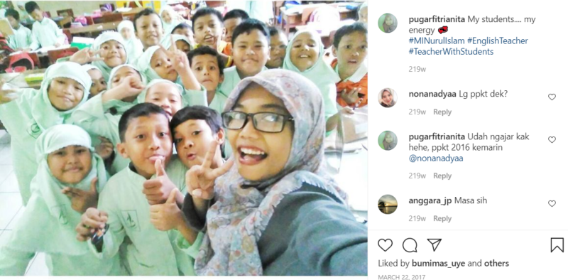 Teacher wearing glasses taking selfie with students in green uniforms