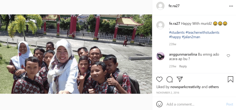 Teacher wearing white taking selfie with students outside school in Indonesia