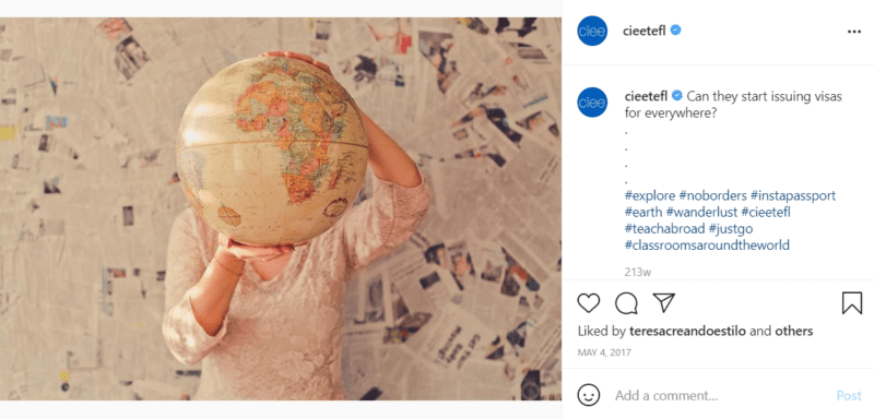 Teacher holding globe covering face with newspapers on the wall