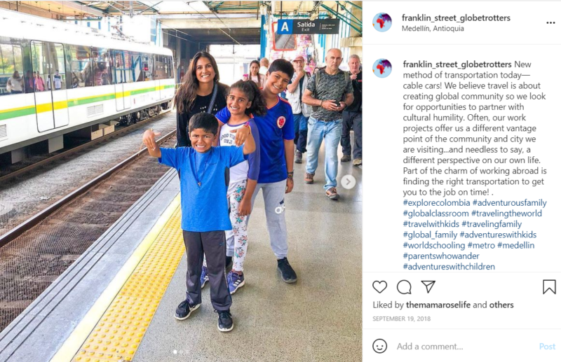 Teacher and students in blue shirts standing on train station platform