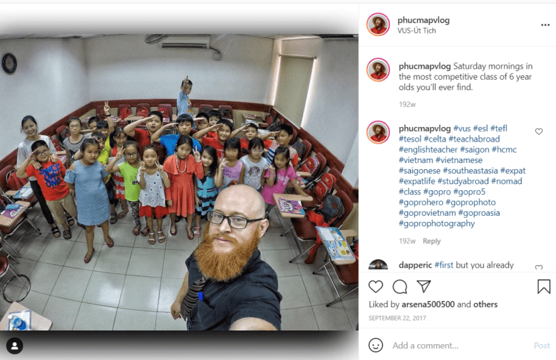 Teacher taking selfie with a large group of young students in classroom