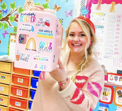 Teacher holding up pink mini fridge in classroom