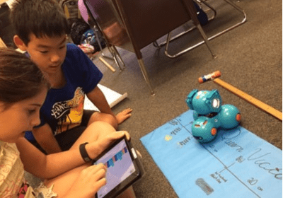 young students using coding and robotics