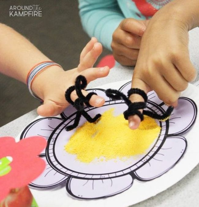 Students wearing pipe cleaner bees on their fingers over a plate of cheese powder