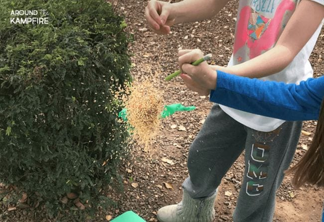 Students exploding a balloon full of seeds and sand