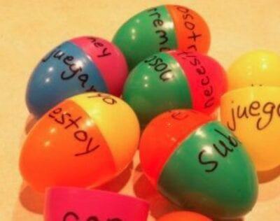 Spanish verbs written on plastic eggs.