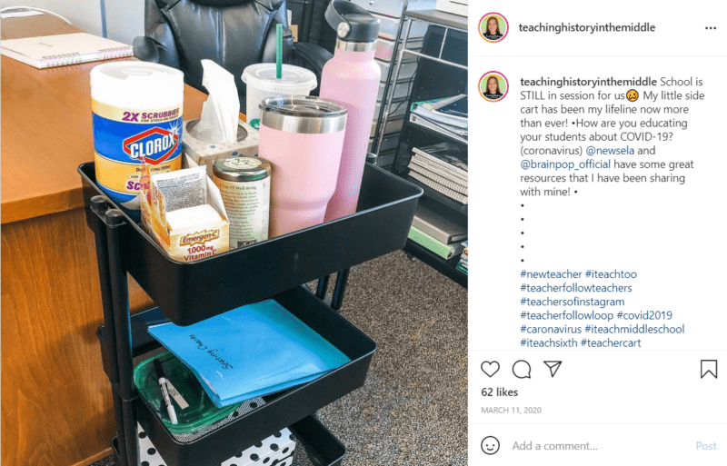 Black teacher cart filled with cleaning supplies and water bottles next to a teacher's desk