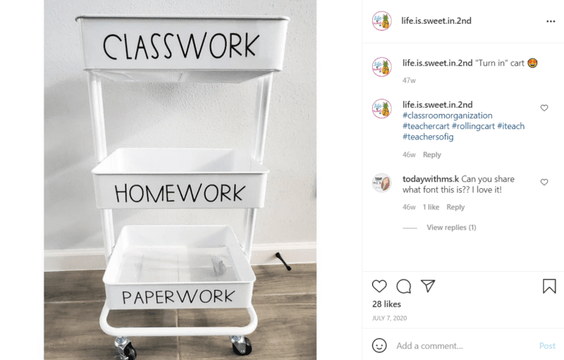 Empty white teacher cart with three racks labeled classwork, homework, and paperwork against a wall