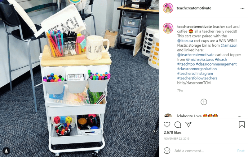 White teacher cart with a desktop on it full of pens, books, and other school supplies located in a classroom