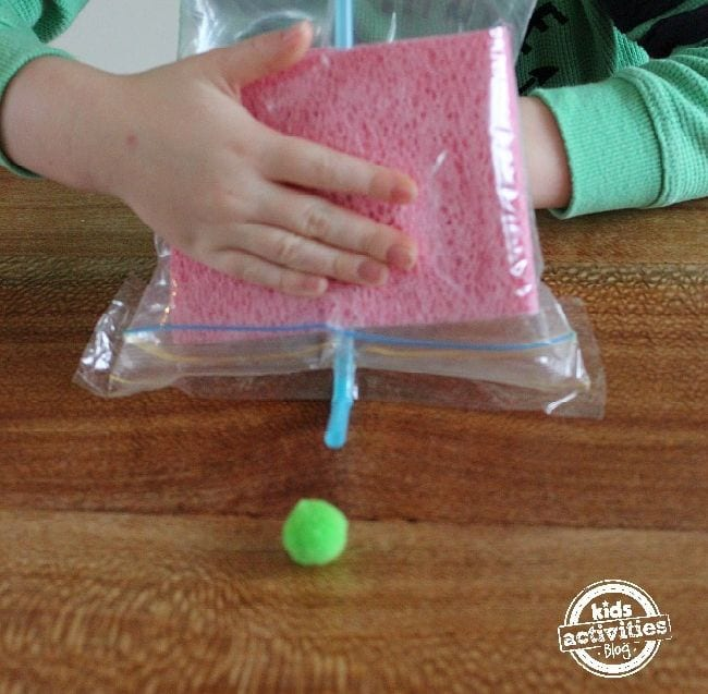 Young student using a straw in a plastic bag with sponges to move a green pompom across a wood table
