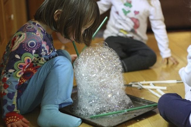 Preschool science student blowing a tower of soap bubbles