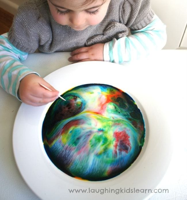 Preschool science student mixing a bowl of colorful milk swirls