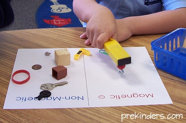 Preschool science student using a bar magnet to test other objects